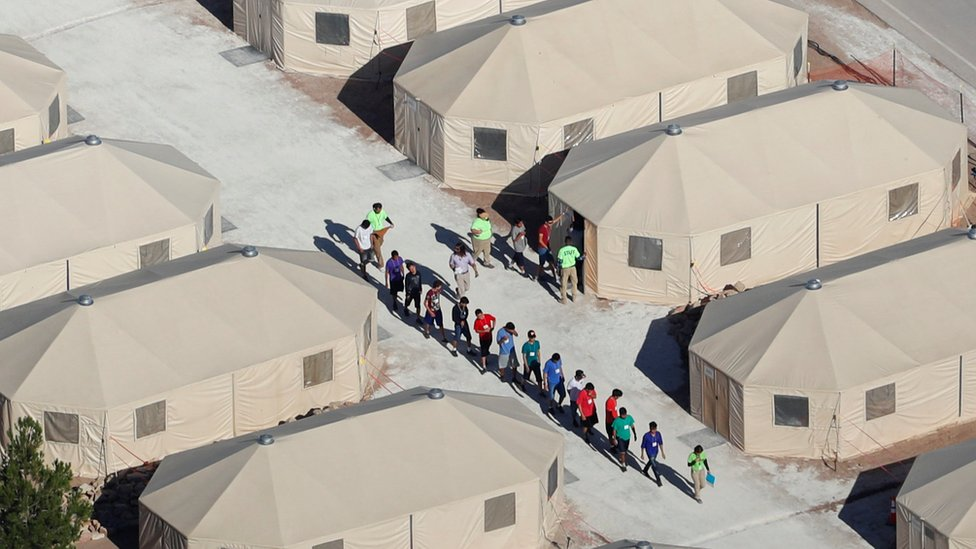 People walking outside tents in Tornillo, Texas