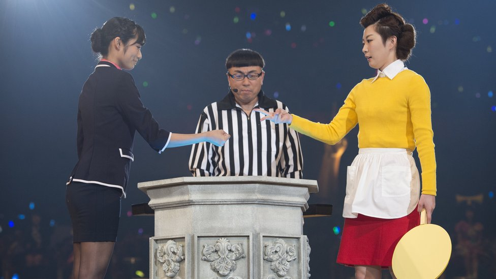 """Two band members compete during the rock-paper-scissors tournament in 2015, with an umpire looking on. The woman on the right has just thrown """"scissors"""", losing to """"rock"""" on the left."""