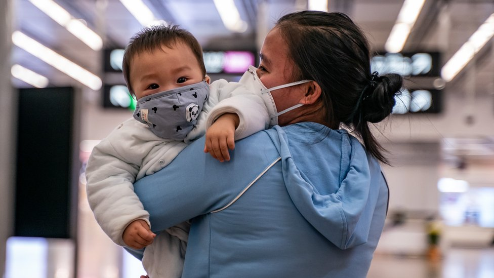 Mother and child in China wearing masks