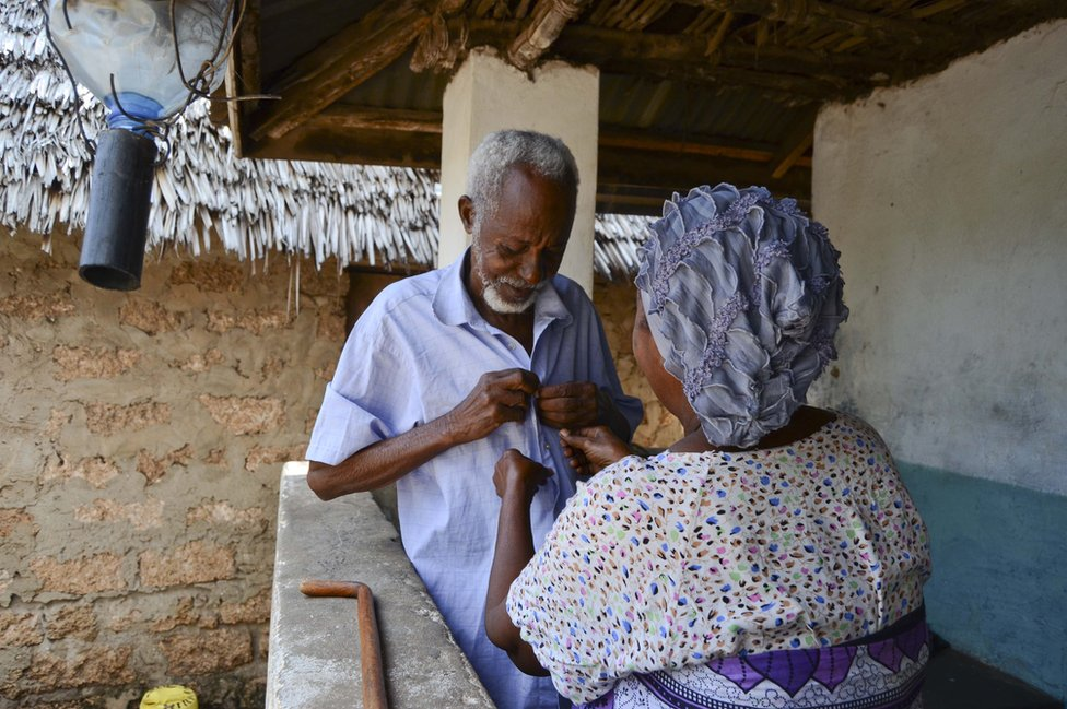 A woman buttons up her husband's shirt in Kenya