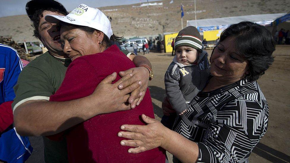 Familiares de los mineros se abrazan tras conocer que los 33 estaban bien y en buen estado de salud.