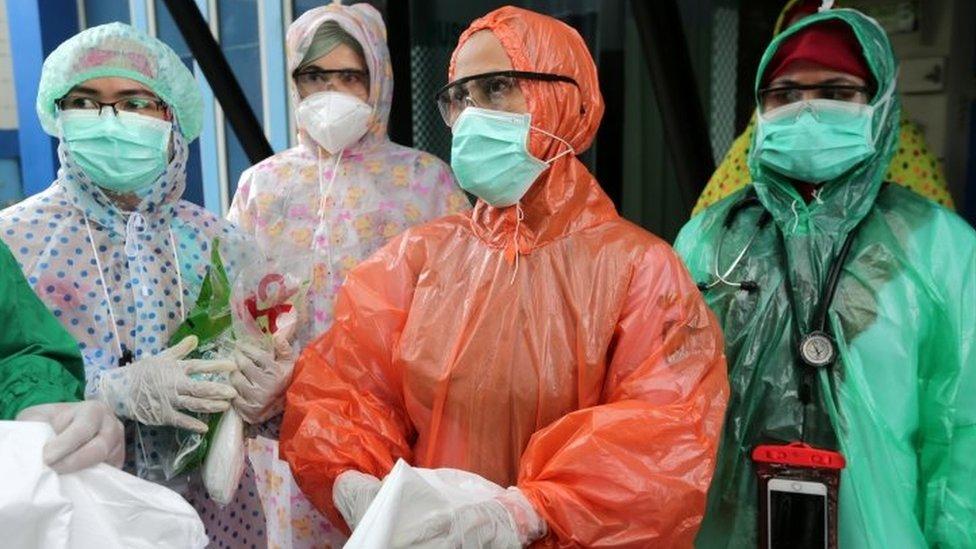 Petugas medis di Banda Aceh mengenakan jas ujan.