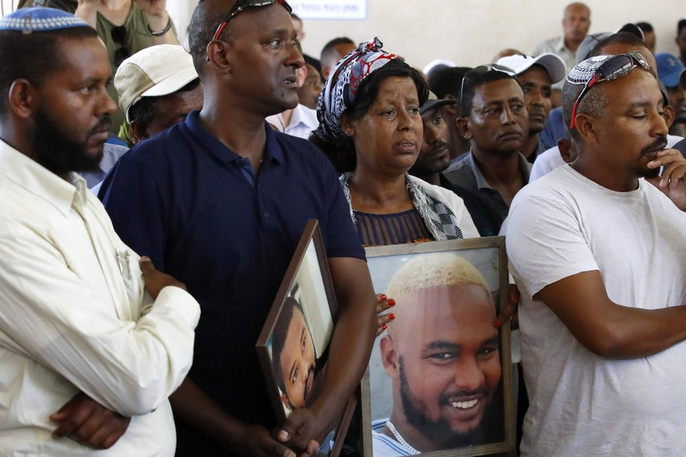 Relatives hold pictures of Solomon Tekah at his funeral in Haifa on 2 July 2019