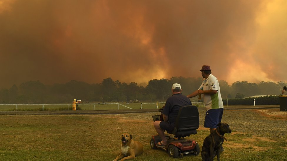 Locals watch as bushfires burn through farmland turning the skies above Nana Glen, 600km north of Sydney a smoky orange.