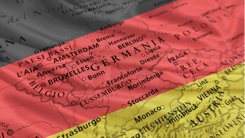 Bandera alemana en el fondo de una parte del mapa de Europa.