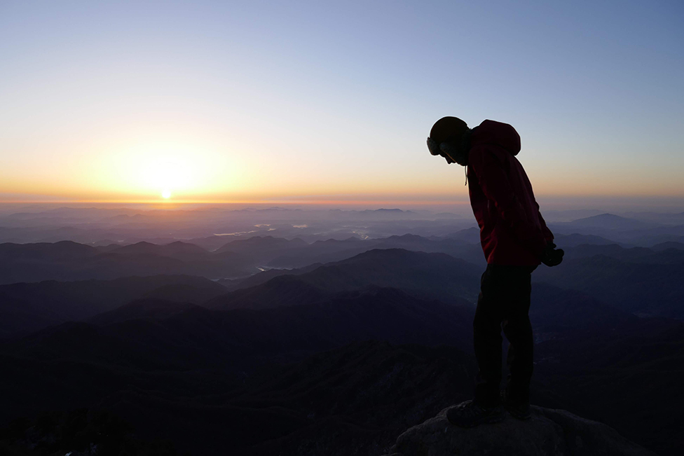A man standing at the top of Mount Jirisan in South Korea.