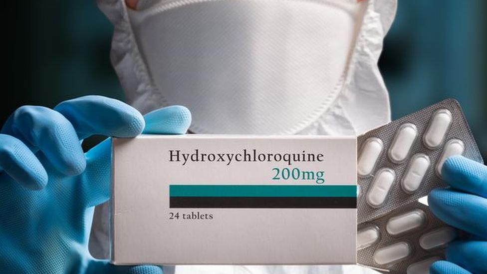 """Profesional de la salud con mascarilla sosteniendo una caja de """"Hydroxychloroquine 200 mg y un blíster con píldoras blancas."""