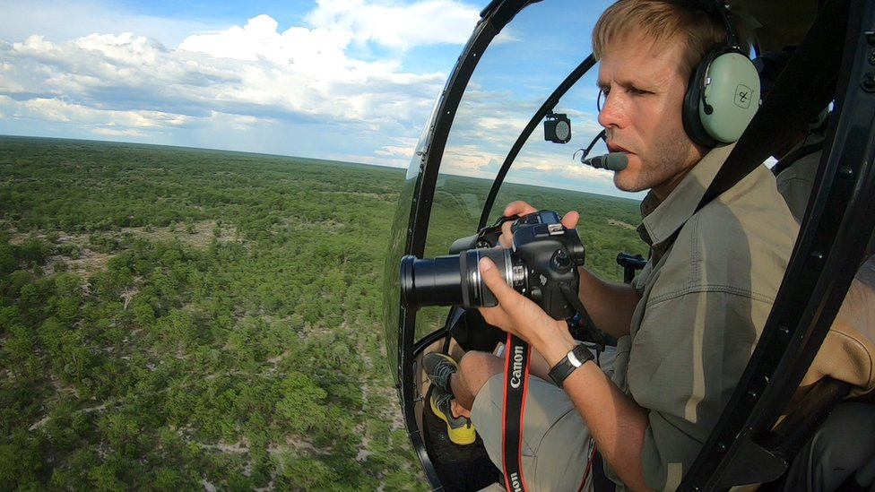 Man taking photographs from a helicopter