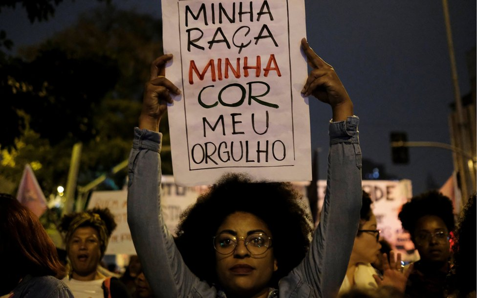 A demonstrator holds a sign during a protest by black women against racism and machismo, 25 July 2018