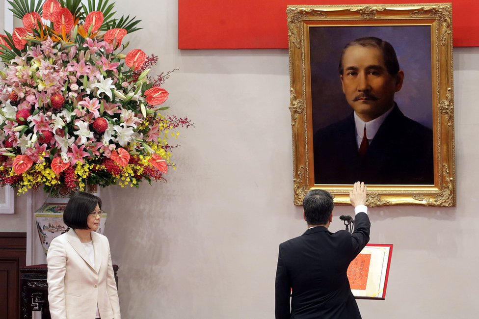 Taiwan's President Tsai Ing-wen (left), standing next to a huge flower display, looks on as Chen Chien-jen swears-in as vice president, holding his right hand up in open-palmed salute, in front of a painting, in Taipei on 20 May 2016
