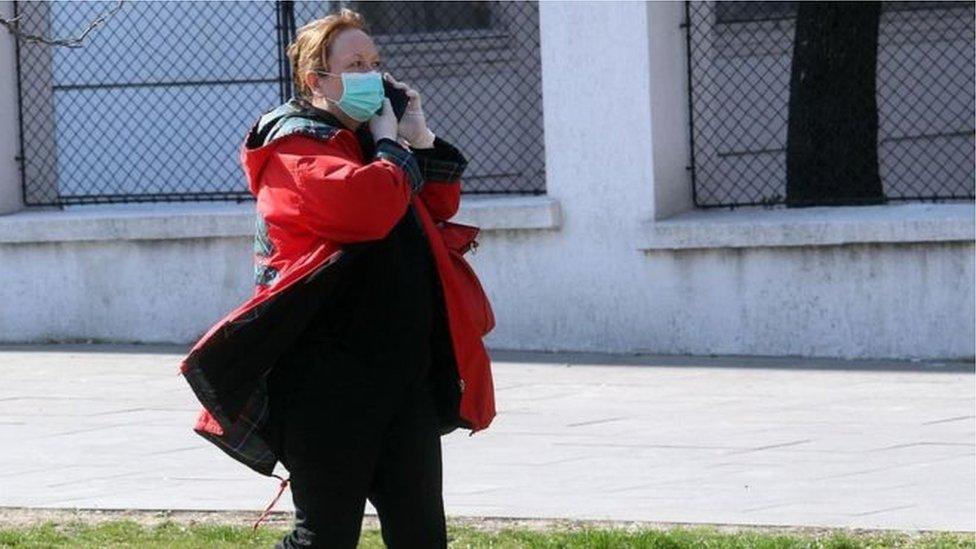 Žena sa maskom na praznoj ulici