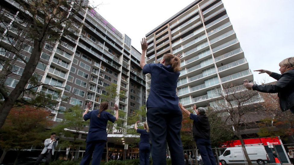 Nurses wave to residents in a Melbourne quarantine hotel