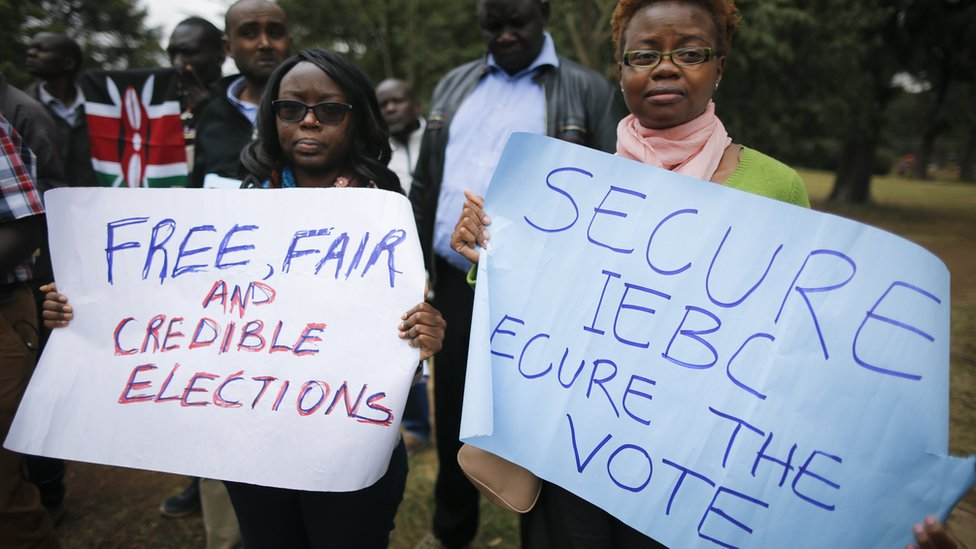 Protesters hold placards calling for free and fair elections