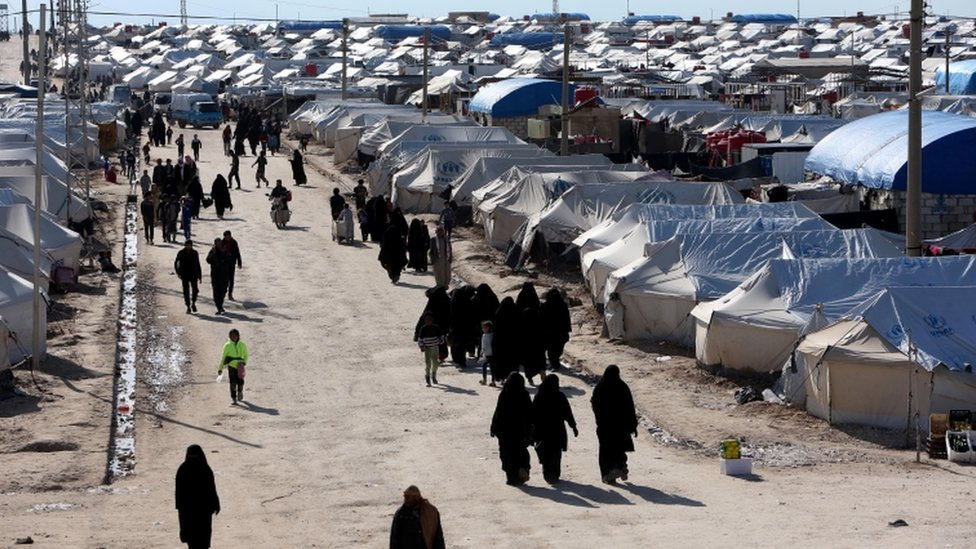 Women walk through al-Hol displacement camp in Hasaka governorate, Syria