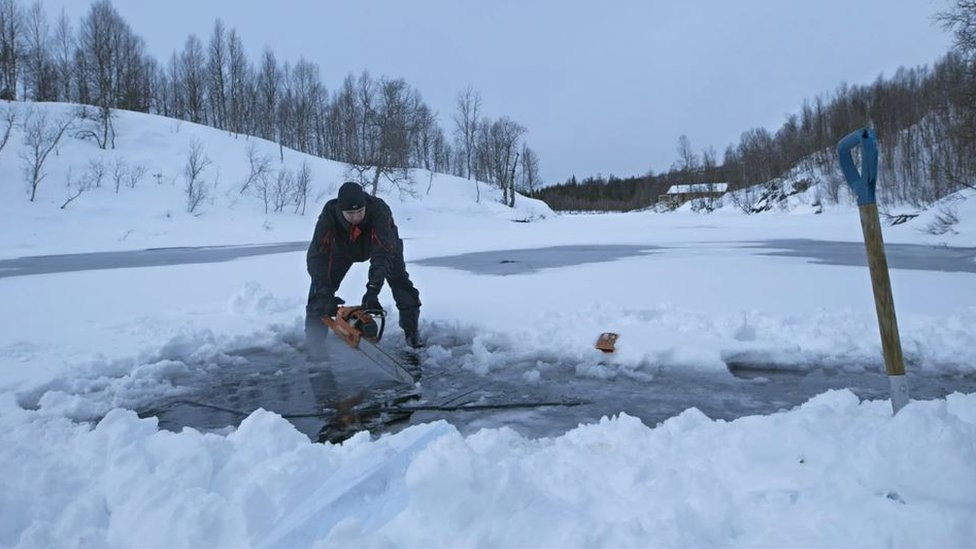 A man with a chainsaw, cutting a hole in the ice at Plura