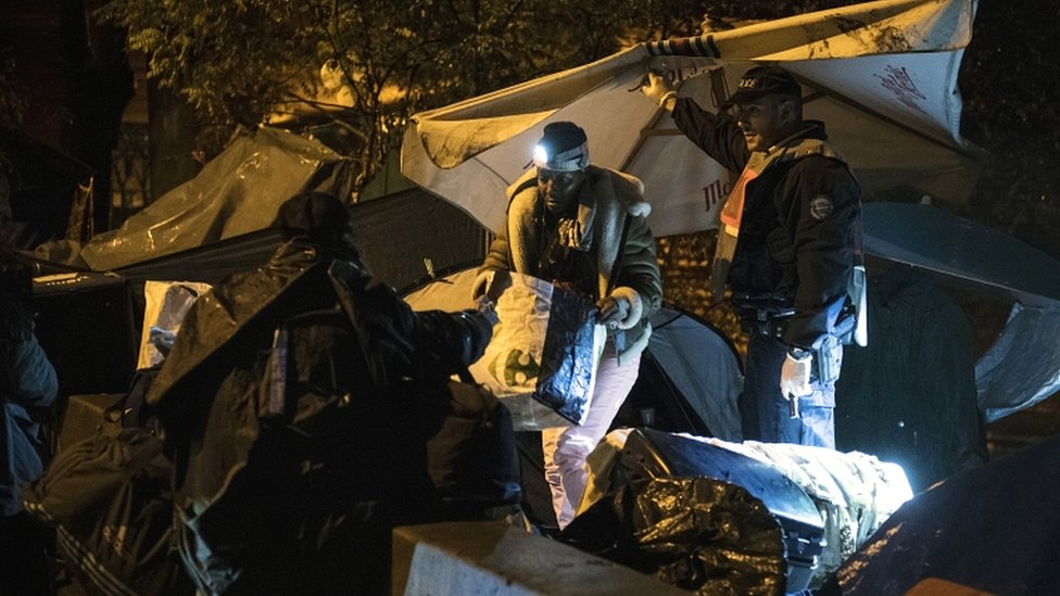 Police inspect tents during a police operation to clear makeshift camps in the north of Paris on 7 November 2019
