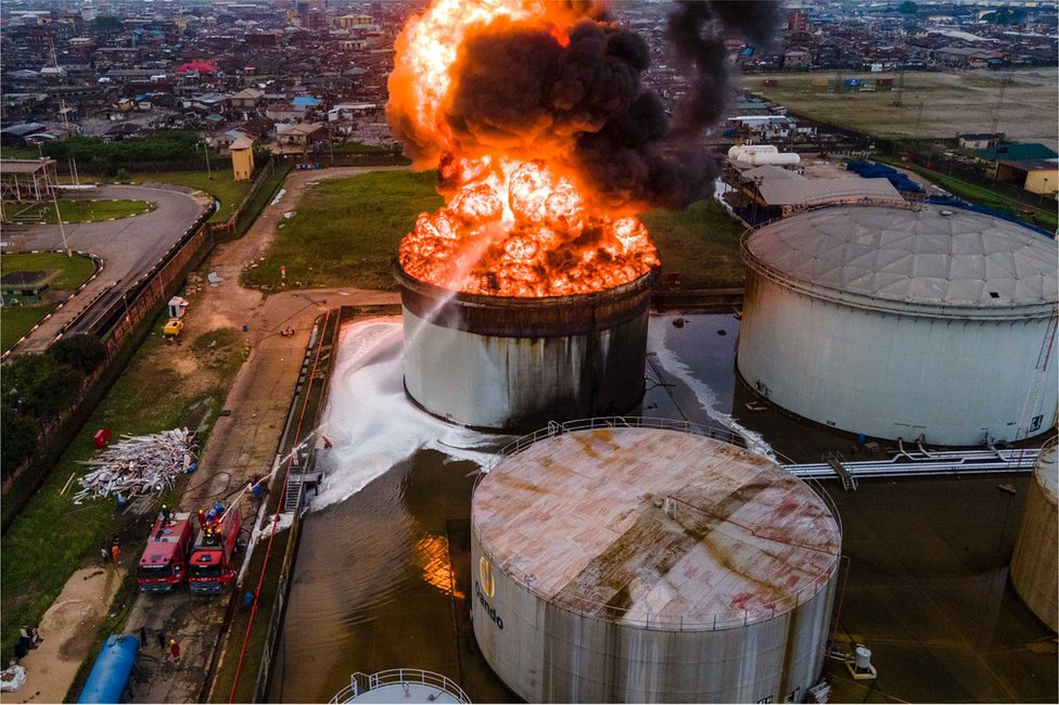 An aerial view of a large oil tanker on fire with fire services trying to control the blaze