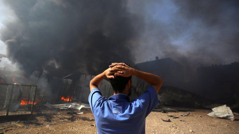 Un hombre cerca de una fábrica de esponjas en llamas tras ser alcanzada por proyectiles de artillería israelíes en Gaza.