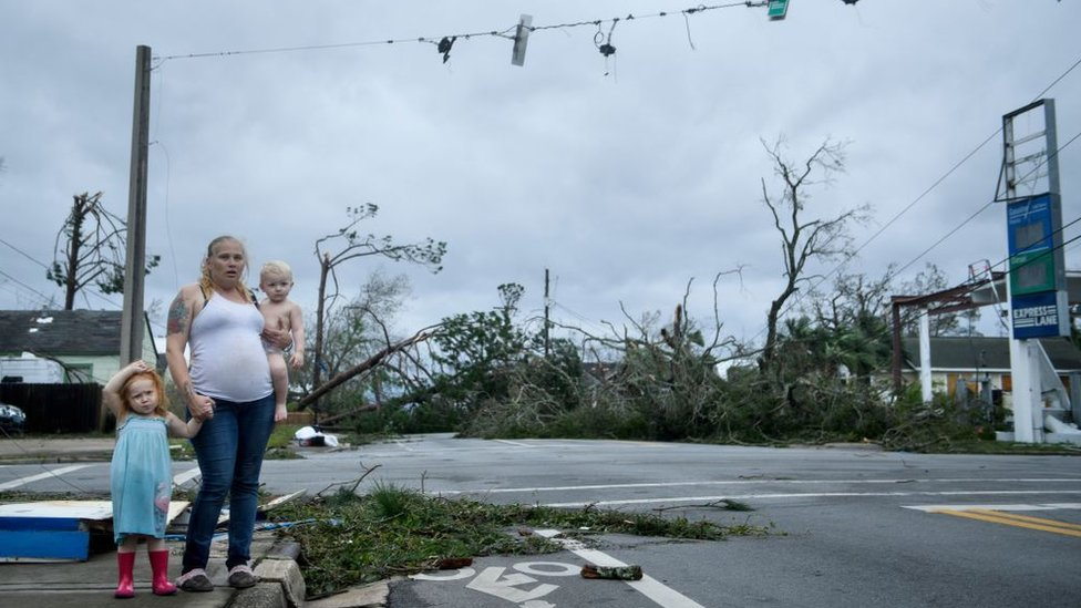 Mujer con sus hijos viendo la destrucción del huracán Michael en una calle