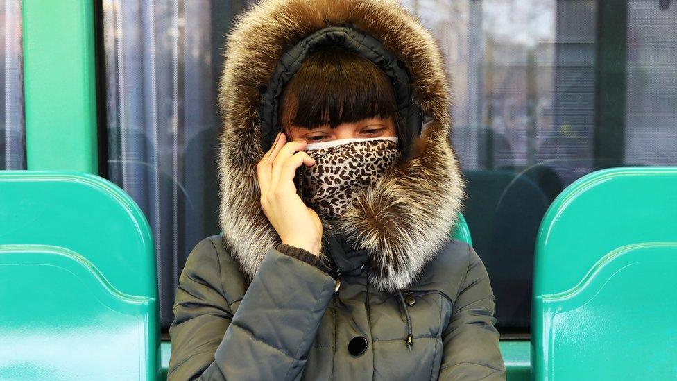 Žena sa maskom priča mobilnim telefonom