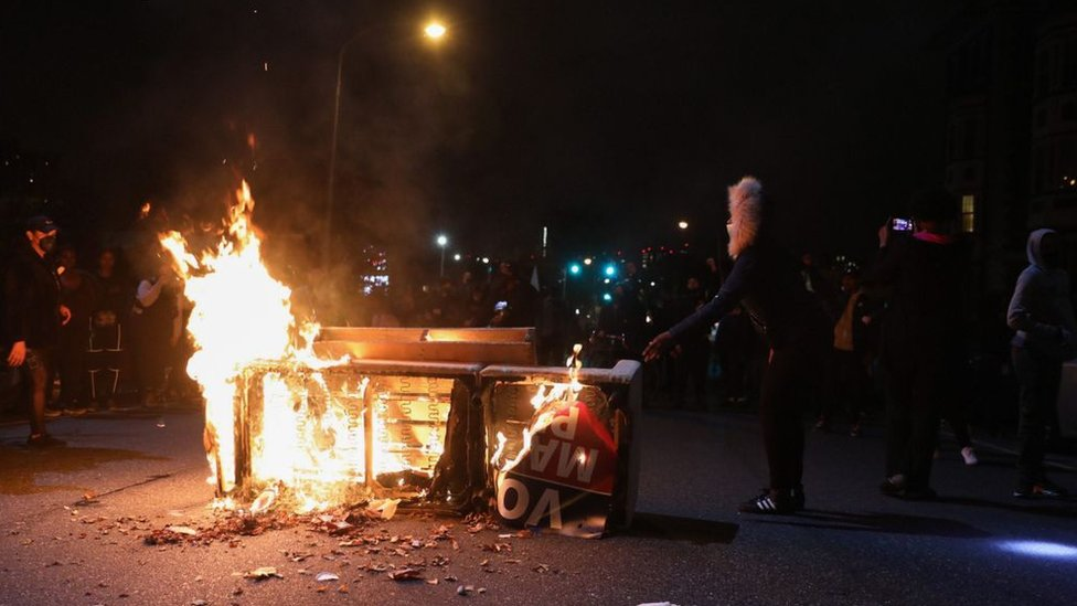 Demonstrators stand near a burning barricade in Philadelphia