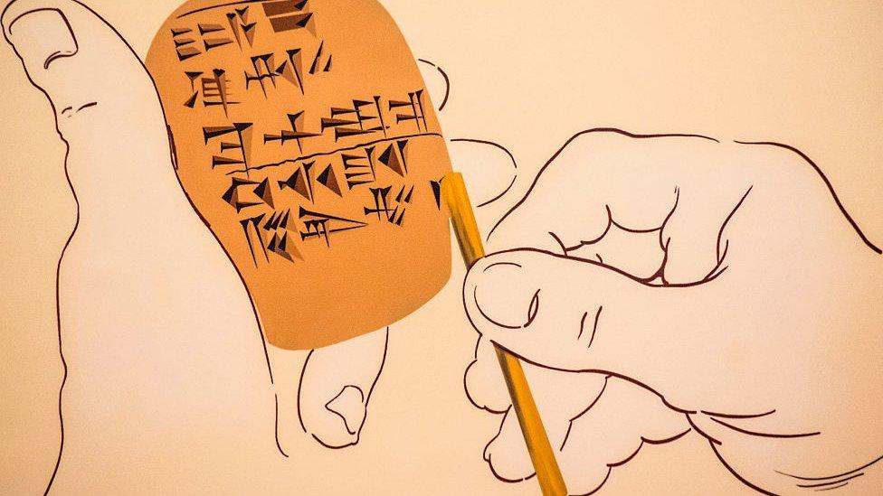 Dibujo que muestra manos sosteniendo tableta de arcilla e imprimiendo símbolos