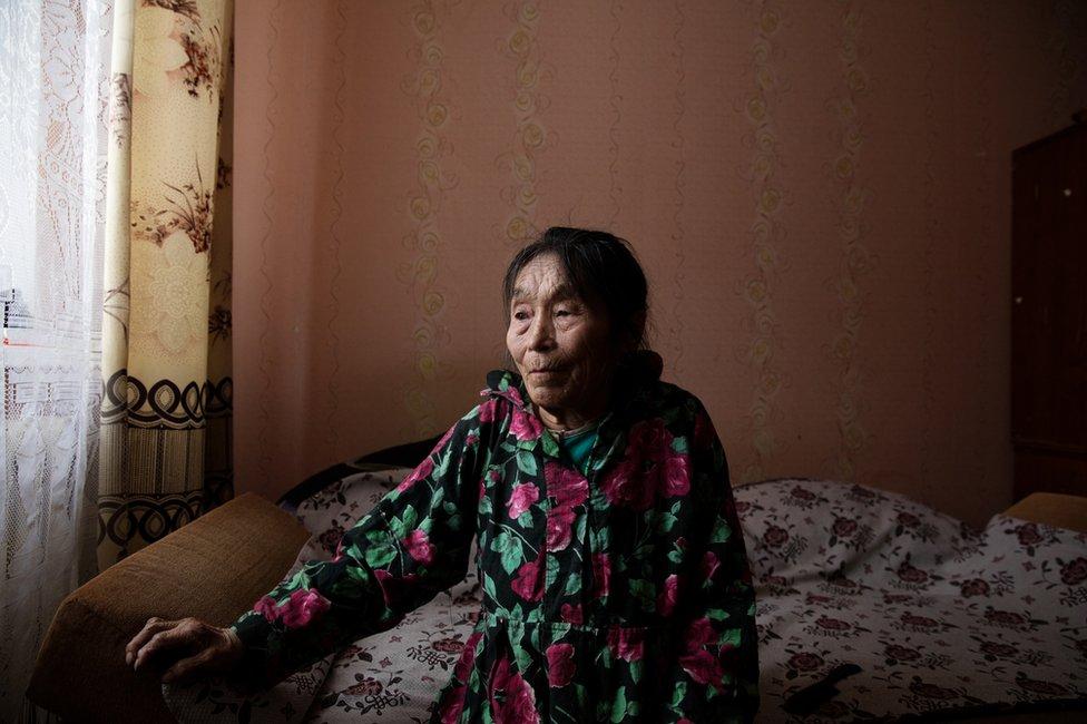 Autipana Audi (born.1941) sitting on her bed in her apartment. Yar-Sale village, Yamal Peninsula, Siberia, Russia.