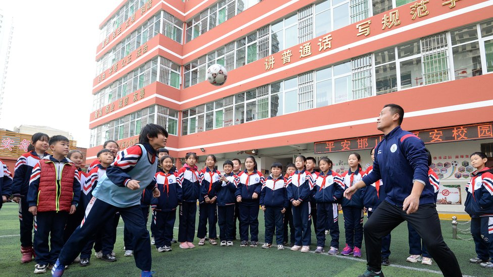 Pupils take part in a football obstacle course in Handan, North China's Hebei Province, Dec. 8, 2020. December 9th is World Football Day.