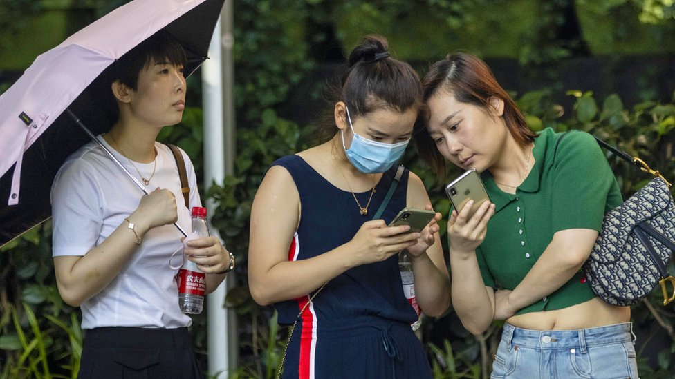 Two women look at mobile phones in the street in Shanghai