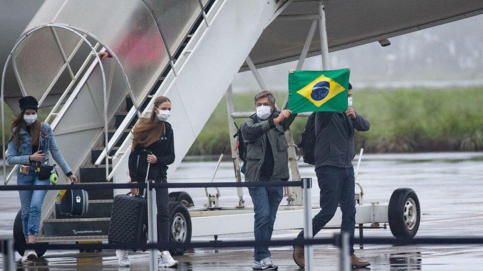 Ciudadanos brasileños bajándose de un avión procedente de China.