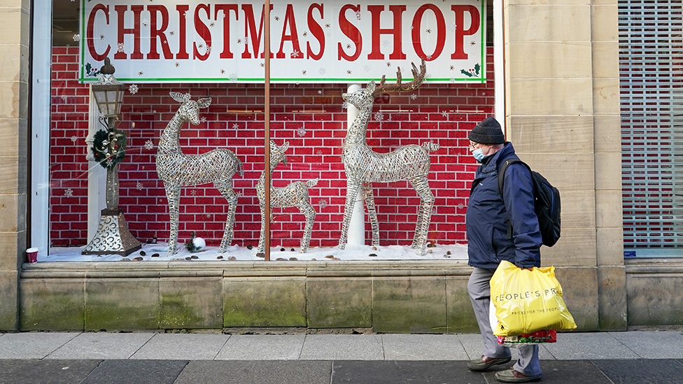 A man walks past a Christmas shop in Newcastle - 2 December 2020