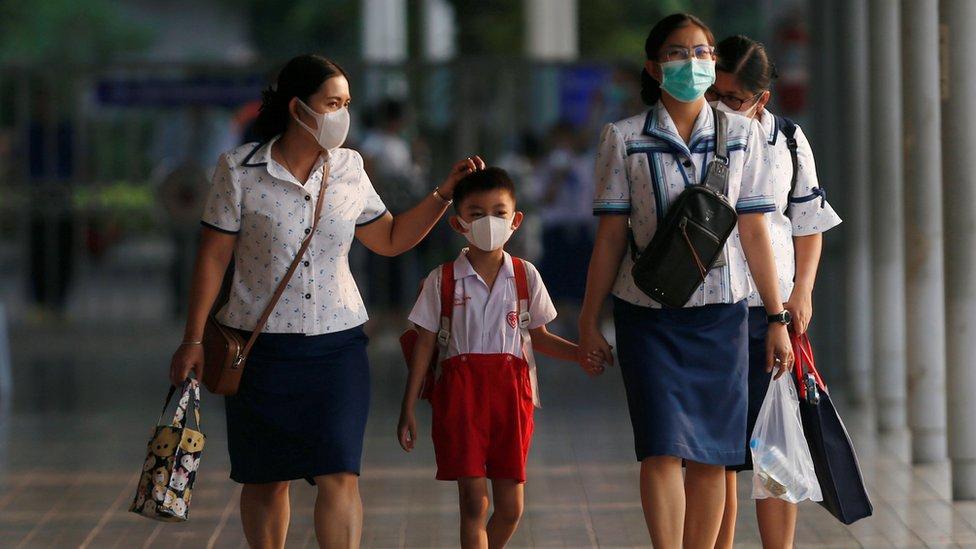 Staff de un colegio tailandés con un alumno, todos portando mascarillas.