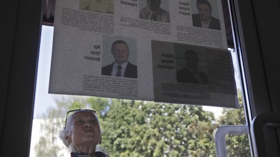 A woman reads official leaflets with biographical details of competing parliamentary candidates in Minsk (11 September 2016)