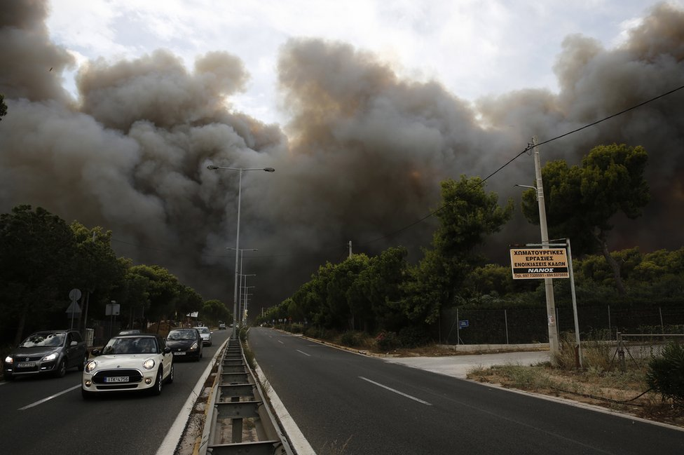 Smoke rises over a motorway in Neo Voutsa, a northeast suburb of Athens