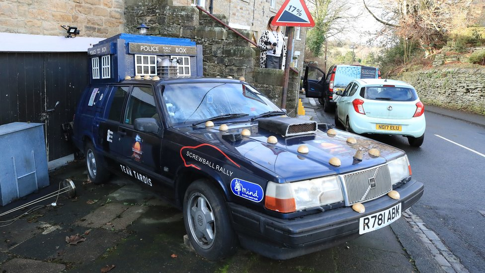 A replica Tardis attached to the top of a vehicle outside the couple's home
