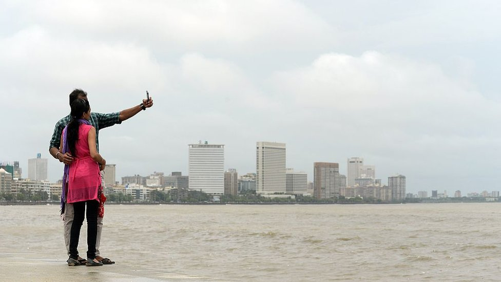 In this photograph taken on June 15, 2015, a young Indian couple take a 'selfie' on Marine Drive promenade in Mumbai.