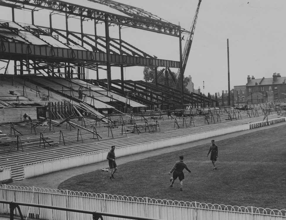 Tottenham Hotspur players Walter Alsford, Michelles and George Greenfield training on the pitch at White Hart Lane in front of where the new East Stand is being built, 26th July 1934