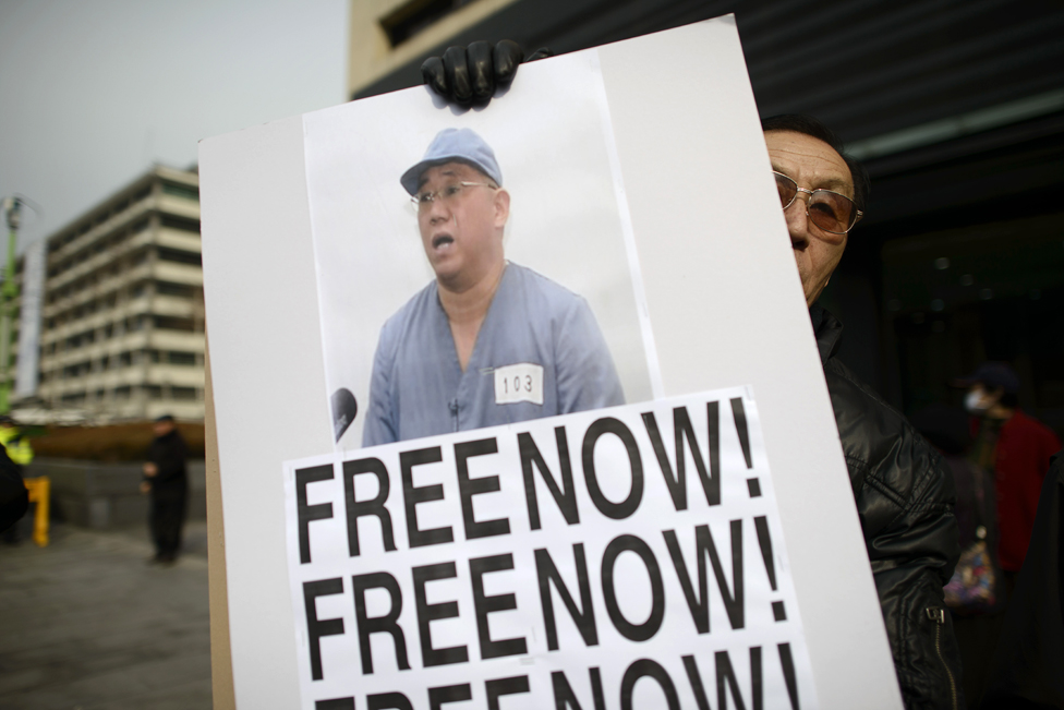 Man holding a placard with Kenneth Bae's photo and the words 'Free now'