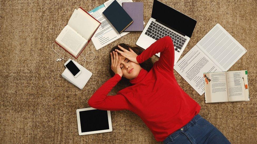 Una joven cansada en el piso con los libros y computadora.