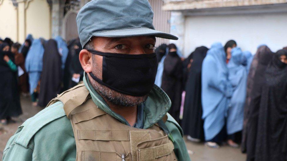 Un soldado vigila a las mujeres que reciben raciones de comida del Programa Mundial de Alimentos en Herat, Afganistán.