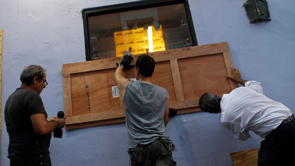 Image shows people boarding up the windows of a business in preparation for Hurricane Maria in San Juan, Puerto Rico on 18 September 2017