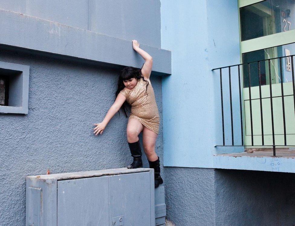 A girl climbs along a wall