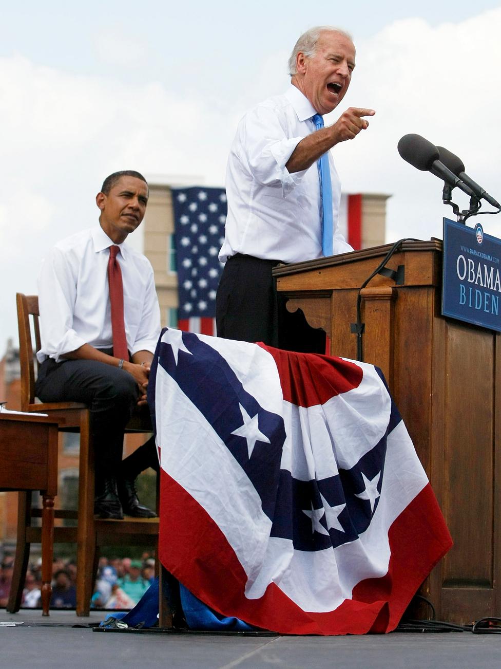 Barak Obama listens Joe Biden on stage