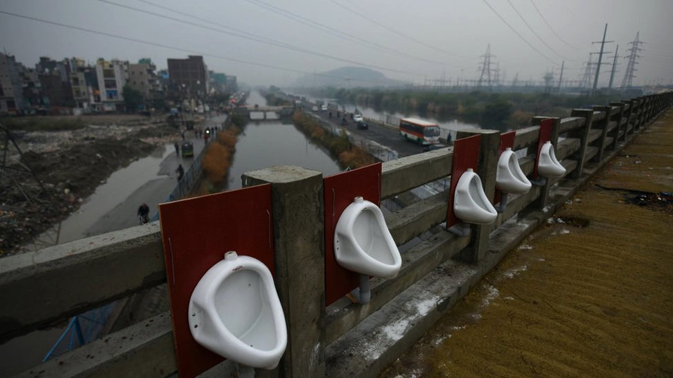 A row of open air public urinals, set up on a bridge spanning over a river and a canal