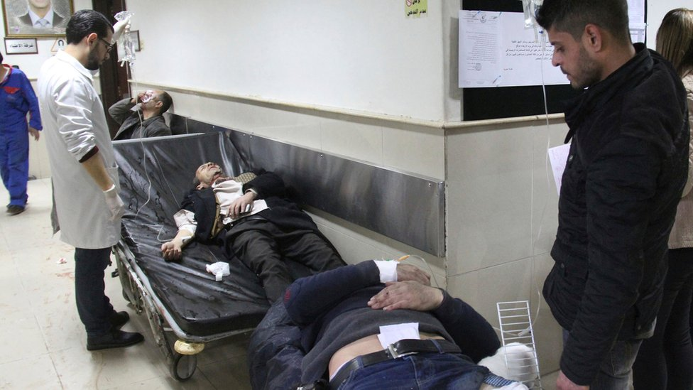 Injured men wait to receive medical treatment after being wounded in a suicide bomb attack at the Palace of Justice in Damascus (15 March 2017)