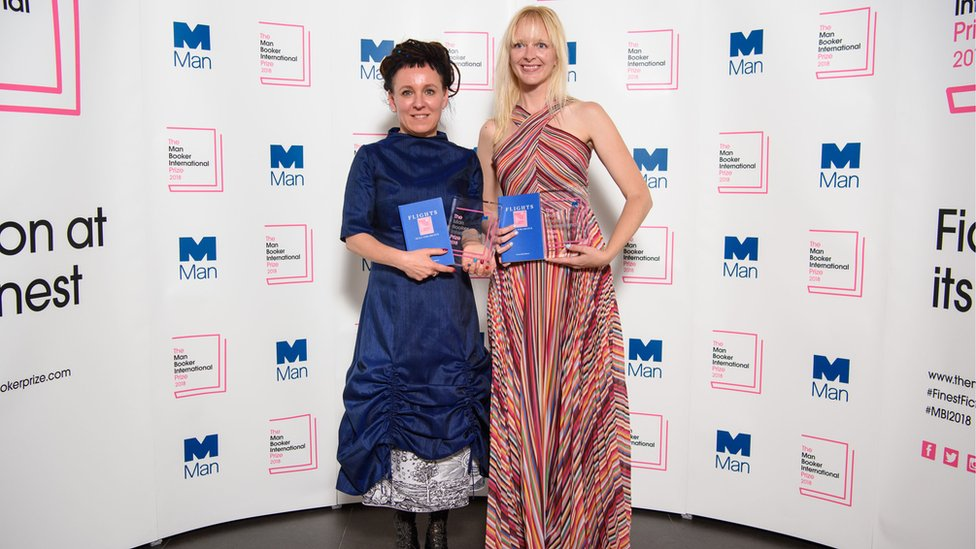 Olga Tokarczuk, left, stands with translator Jennifer Croft holding copies of Flights and the prize at the award ceremony on 22 May 2018