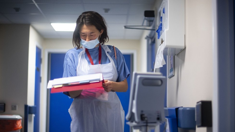 A doctor looks at a patient's notes at NHS Seacole Centre in Surrey