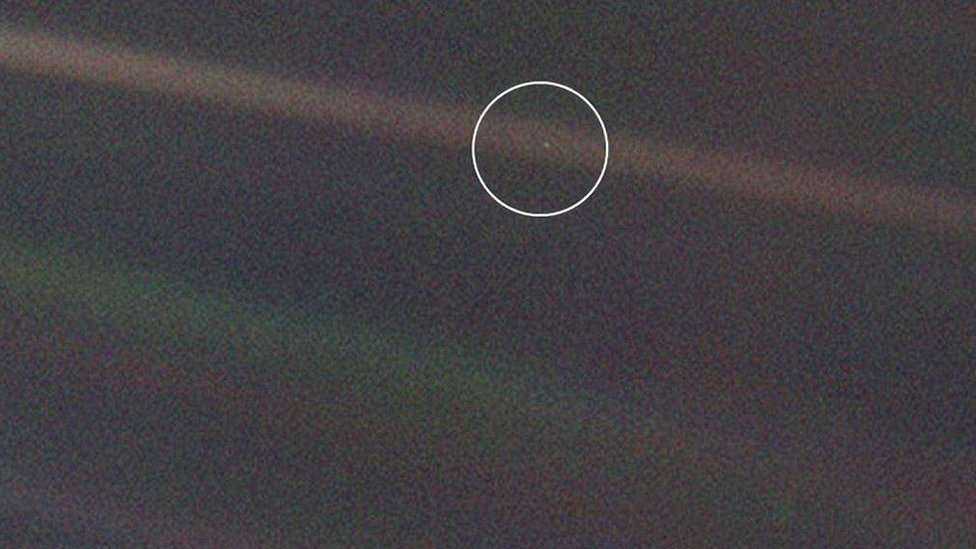 Imagen de la Tierra tomada por Voyager 1, donde se ve a nuestro planeta como un pequeño punto azul en un vasto océano cósmico
