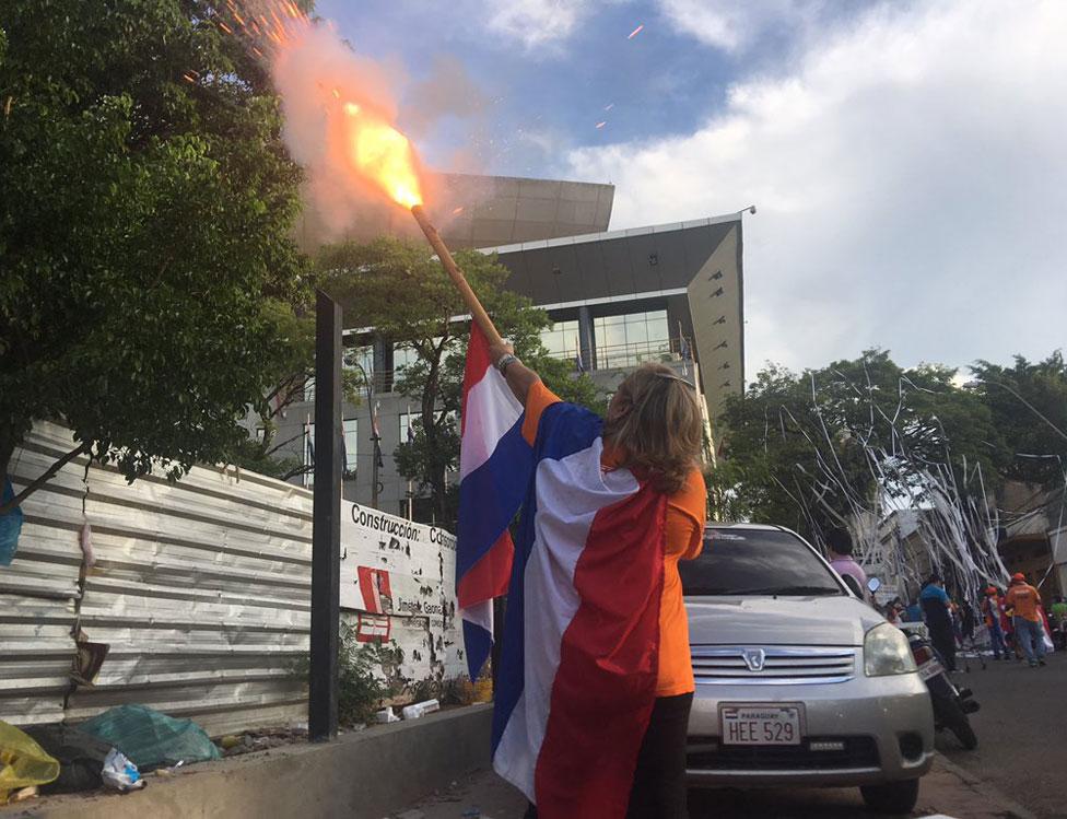 Una mujer lanza un petardo fuera del Congreso de Paraguay