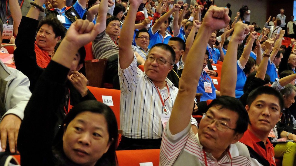 Members of Taiwan's ruling Kuomintang (KMT), raise fists during the party congress in Taipei on October 17, 2015.